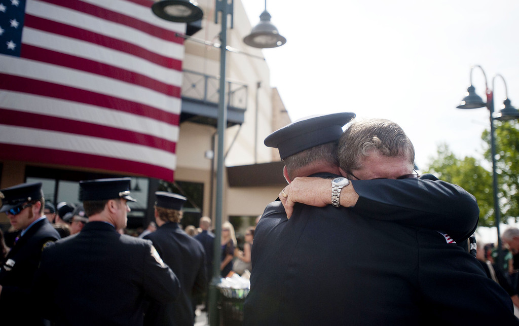 Description of . Chaplain Bob Ossler (R) with the Mayer, Arizona fire department hugs people at the entrance to a memorial service honoring the 19 firefighters killed in a wildfire at Tim's Toyota Center July 9, 2013 in Prescott Valley, Arizona. T(Photo by Laura Segall/Getty Images)