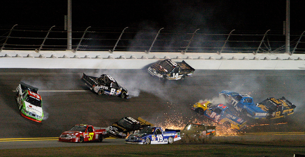Description of . Tim George Jr. (5), Max Gresham (8), Brennan Newberry (14) and others get caught up in a crash as Norm Benning (57) and Ross Chastain (19) try to avoid the mess during the NASCAR Truck Series auto race at Daytona International Speedway, Friday, Feb. 22, 2013, in Daytona Beach, Fla. (AP Photo/Darryl Graham)