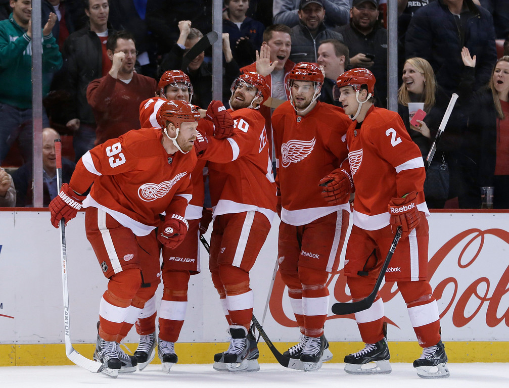 Description of . Detroit Red Wings left wing Johan Franzen (93), of Sweden, is congratulated by teammates after scoring during the second period of an NHL hockey game against the Colorado Avalanche in Detroit, Tuesday, March 5, 2013. (AP Photo/Carlos Osorio)