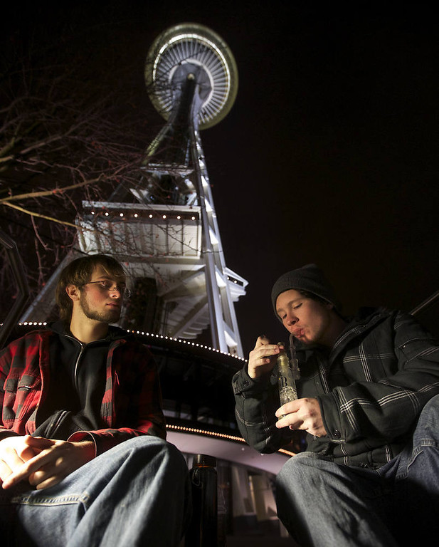 Description of . Dustin, left, and Paul of Tacoma, Washington, both of which declined to give their last names, share a water pip underneath the Space Needle shortly after a law legalizing the recreational use of  marijuana took effect on December 6, 2012 in Seattle, Washington.  Voters approved an initiative to decriminalize the recreational use of marijuana making it one of the first states to do so. (Photo by Stephen Brashear/Getty Images)