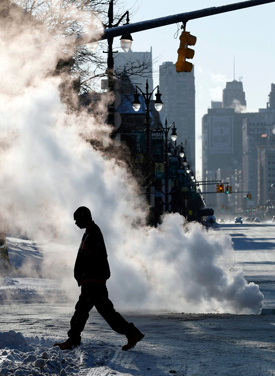Description of . A man crosses Woodward Avenue in front of a steam vent in Detroit, Michigan, USA, 07 January 2014. A deep freeze threatened much of the eastern US seaboard on 07 January as the mercury plunged into lows not seen in nearly two decades, government forecasters said. 'Dangerously cold Arctic air' will be descend on the eastern two-thirds of the nation after gripping northern and mid-western states since 05 January, the National Weather Service warned.  EPA/JEFF KOWALSKY