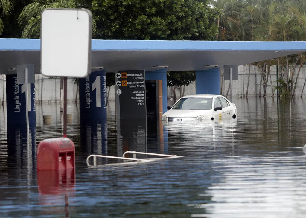 Description of . Partial view at the airport of Acapulco, Guerrero state, Mexico, on September 17, 2013 flooded by heavy rains that have been hitting the country. Mexican authorities scrambled Tuesday to launch an air lift to evacuate tens of thousands of tourists stranded amid floods in the resort of Acapulco following a pair of deadly storms. At least 48 people were killed and thousands evacuated from towns on the Pacific and Gulf of Mexico coasts over the weekend as Tropical Storm Manuel and downgraded Hurricane Ingrid set off landslides and floods that damaged bridges, roads and homes. Pedro PARDO/AFP/Getty Images