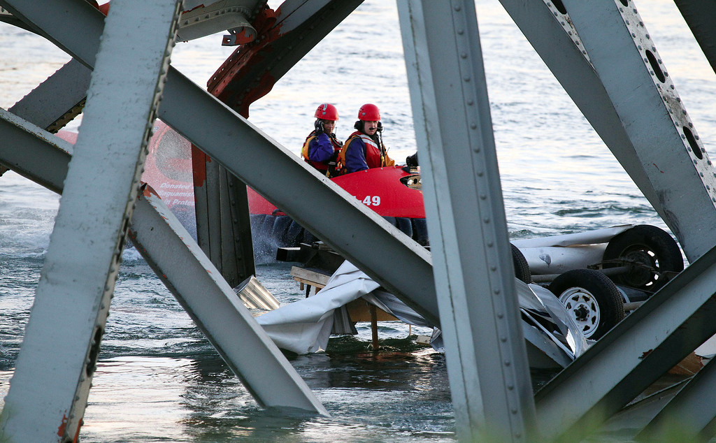 Description of . A hover craft crew examines a upside down car as they look for victims after a portion of the Interstate 5 bridge collapsed into the Skagit River in Mount Vernon, Wash., Thursday, May 23, 2013. (AP Photo/Everett Daily Herald, Jennifer Buchanan)