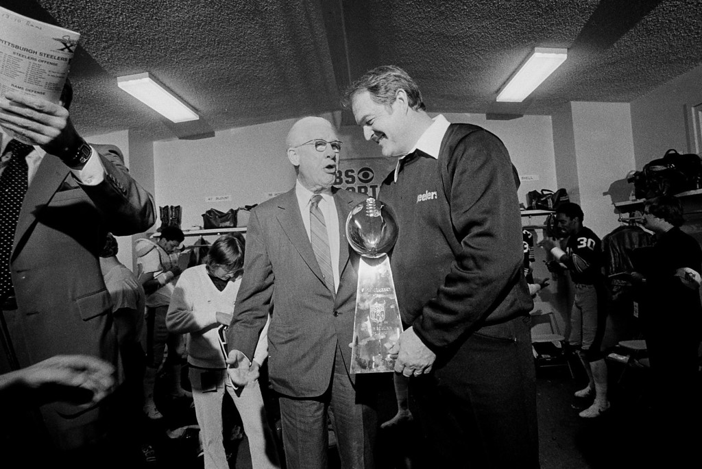 Description of . Pittsburgh Steelers' board chairman Art Rooney, left, talks with Steelers' coach Chuck Noll after presentation of the Super Bowl XIV trophy in the Steelers' locker room at the Rose Bowl in Pasadena, Calif., Jan. 20, 1980.  (AP Photo/Harry Cabluck)