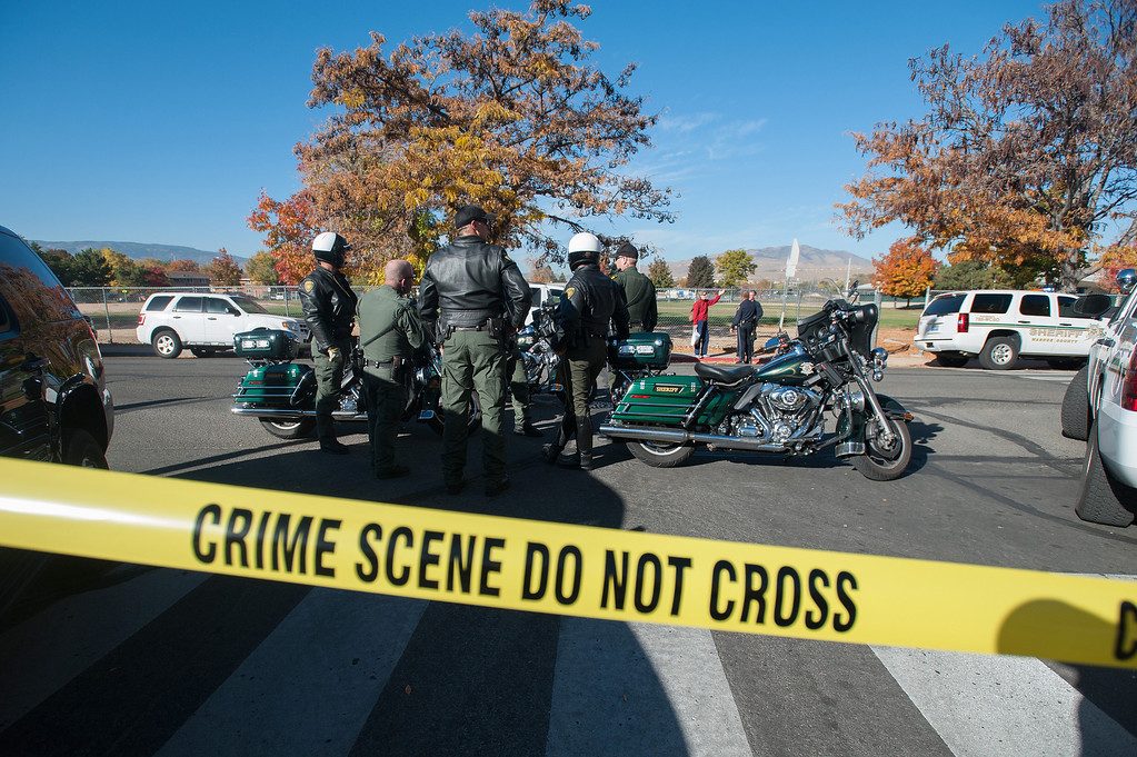 Description of . Police secure the scene near Sparks Middle School after a shooting in Sparks, Nev., on Monday, Oct. 21, 2013.   (AP Photo/Kevin Clifford)