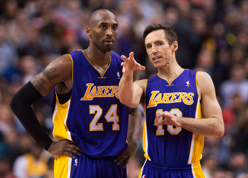 Description of . Los Angeles Lakers guards Kobe Bryant, right, and Steve Nash, right, talk during a time-out while playing against the Toronto Raptors during first half NBA basketball action in Toronto on Sunday Jan. 20, 2013. (AP Photo/THE CANADIAN PRESS,Nathan Denette)