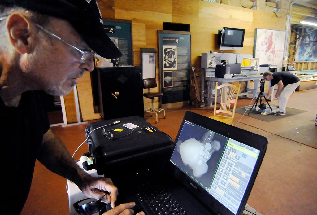 Description of . In this Sept. 4, 2013 photo, explorer Barry Clifford, left, reviews an X-ray image of a concretion showing a cannon ball and coins that diver and conservator Chris Macort, right, had recorded in Brewster, Mass. The concretion is some of the new treasure recovered around the wreck of the Whydah, a pirate ship that sank during a ferocious storm off Cape Cod in 1717. Clifford located the Whydah site in 1984 and has since documented 200,000 artifacts. He only recently got indications there may be far more coins than the roughly 12,000 he's already documented. (AP Photo/Cape Cod Times, Merrily Cassidy)