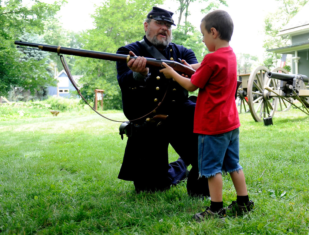 Description of . Daniel Webb of Farmington, dressed as a member of  Dygerts Company of Sharp Shooters, shows Daniel Stinson, 6, of Northville, Mich., how to shoot his 1863 Remington Contract Rifle. Photos of Northville, Mich., Fourth of July celebration called