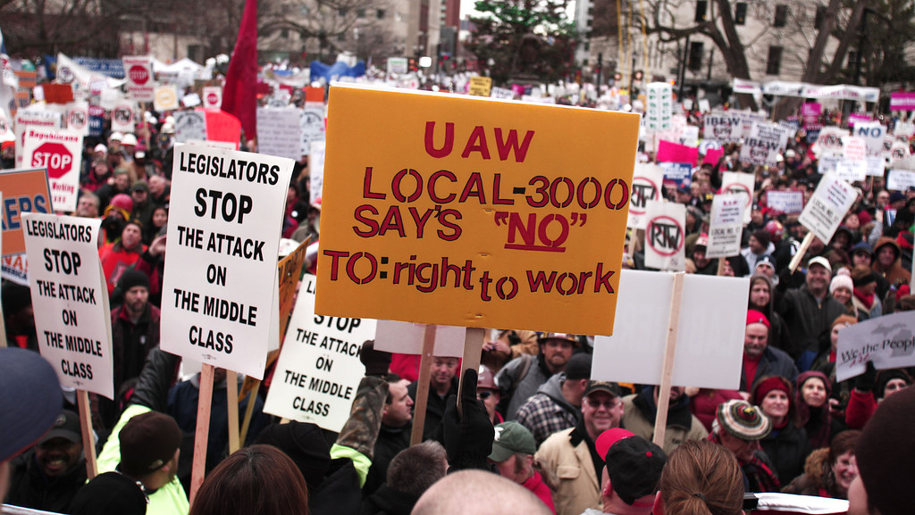 Description of . Union members from around the country rally at the Michigan State Capitol to protest a vote on Right-to-Work legislation December 11, 2012 in Lansing, Michigan. Republicans control the Michigan House of Representatives, and Michigan Gov. Rick Snyder has said he will sign the bill if it is passed. The new law would make requiring financial support of a union as a condition of employment illegal. (Photo by Bill Pugliano/Getty Images)