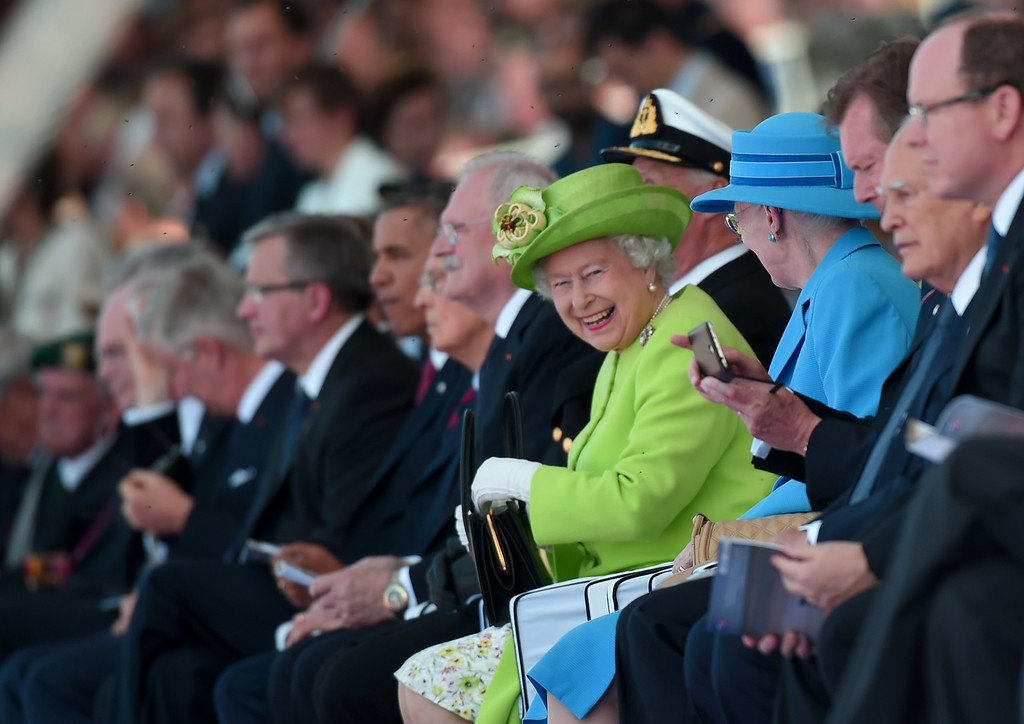 Description of . Britain's Queen Elizabeth II (c) smiles next to Danish Queen Margrethe (R) during the international D-Day commemoration ceremony on the beach of Ouistreham, Normandy, on June 6, 2014, marking the 70th anniversary of the World War II Allied landings in Normandy.   AFP PHOTO / DAMIEN MEYER/AFP/Getty Images