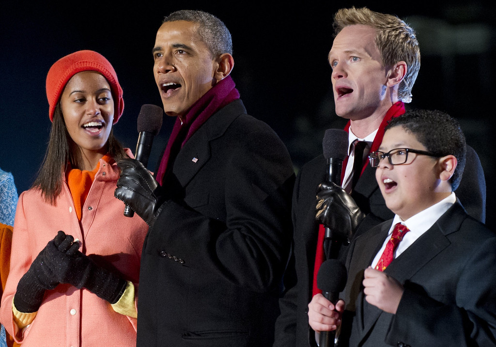 Description of . US President Barack Obama (2nd L) alongside his daughter Malia (L), sing with actor Neil Patrick Harris (2nd R) and actor Rico Rodriguez (R) from the televison show