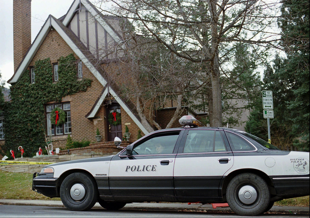 . A police officer sits in her cruiser on Friday, Jan. 3, 1997, outside the home in which 6-year-old JonBenet Ramsey was found murdered in Boulder, Colorado on Dec. 26, 1996. (AP Photo/David Zalubowski)