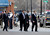 New York Gov. Andrew Cuomo, right, walks to a vehicle as law enforcement officers take cover along Main Street after shots were fired while they were searching for a suspect in two shootings that killed four and injured at least  two on, Wednesday, March 13, 2013, in Herkimer, N.Y.(AP Photo/Mike Groll)
