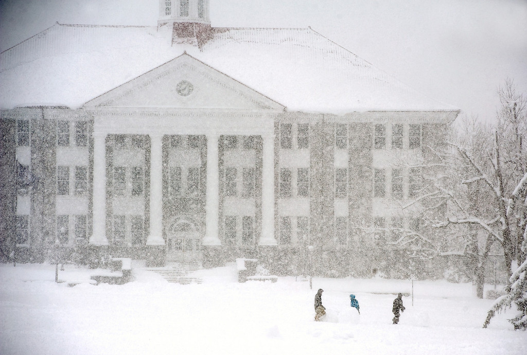 Description of . Three people walk the James Madison University Quad, with Wilson Hall pictured in the background, during the snow storm Wednesday morning, March 6, 2013 in Harrisonburg, Va. (AP Photo/Daily News-Record, Nikki Fox)