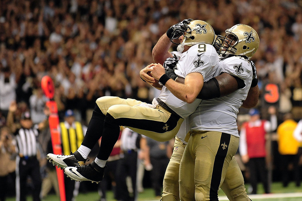 Description of . Ben Grubbs #66 of the New Orleans Saints celebrates a touchdown with Drew Brees #9 during a game against the Arizona Cardinals at the Mercedes-Benz Superdome on September 22, 2013 in New Orleans, Louisiana.  The Saints defeated the Cardinals 31-7.  (Photo by Stacy Revere/Getty Images)