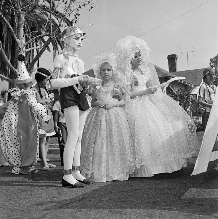 Description of . Pictured here is the Halloween festival in Anaheim, Calif., Oct. 20, 1962. Nearly everyone  turns out to watch the parade, and thousands are on hand to watch the show that launches it at the Palma Stadium. Another 7,000 or more school children take part in a youngsters' parade and there is breakfast for 2,000 costumed citizens.  (AP Photo)
