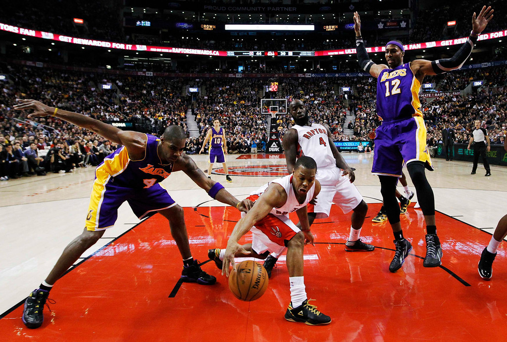 Description of . Toronto Raptors' Kyle Lowry (center L) and Quincy Acy (center R) battle for the ball with Los Angeles Lakers' Antawn Jamison (4) and Dwight Howard (12) during the first half of their NBA basketball game in Toronto, January 20, 2013.     REUTERS/Mark Blinch