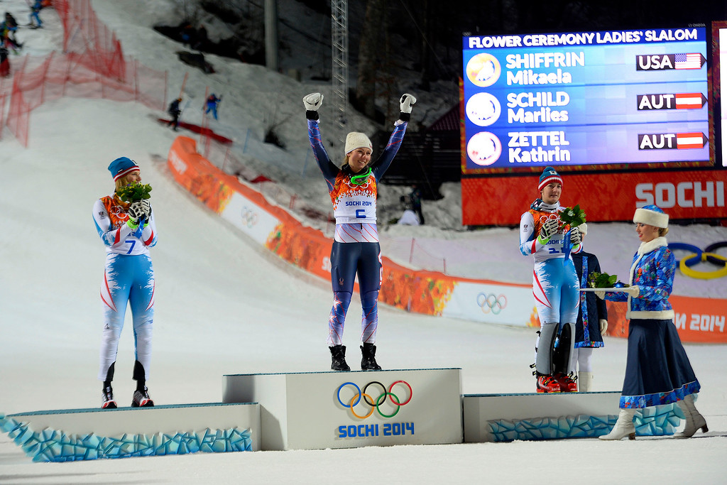 Description of . Gold medalist American Mikaela Shiffrin raises her hands as she is announced while silver medalist Marlies Schild (left) and bronze medalist Kathrin Zettel (both of Austria) look on after ladies' slalom run 2. Sochi 2014 Winter Olympics on Friday, February 21, 2014 at Rosa Khutor Alpine Center. (Photo by AAron Ontiveroz/ The Denver Post)