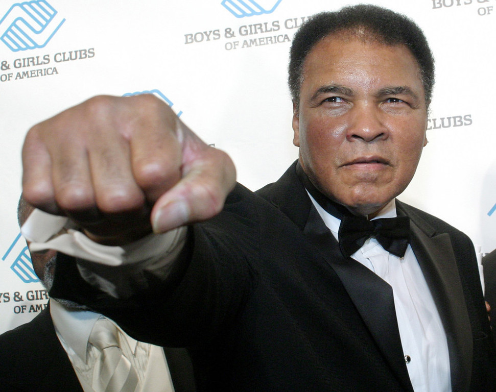 Description of . Boxing legend Muhammad poses at the Boys & Girls Clubs of America annual President's dinner on June 9, 2004 in New York. A small leather-bound volume in which Ali drew pictures of himself fighting arch rival Joe Frazier has sold for $30,000 at auction in London on Monday, Nov.1, 2004.(AP Photo/Tina Fineberg)