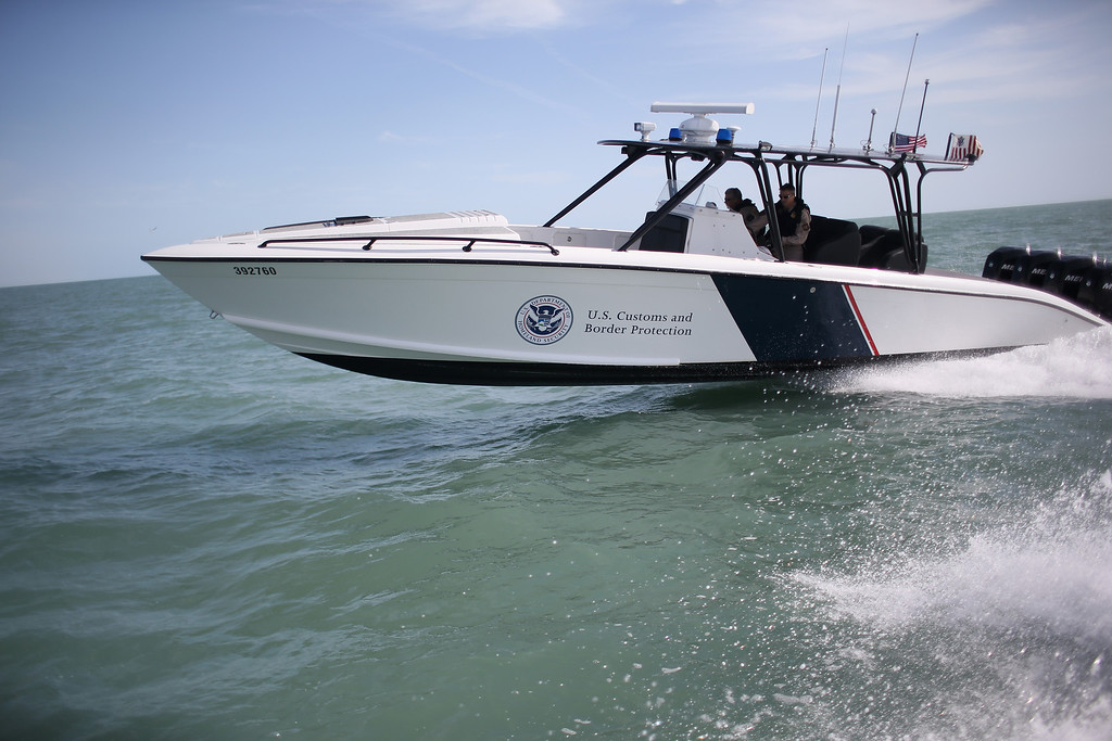 Description of . PORT ISABEL, TX - APRIL 12:  A boat crew from the U.S. Office of Air and Marine (OAM) races through the Gulf of Mexico on April 12, 2013 near Port Isabel, Texas. The crew patrols coastline waters near the U.S.-Mexico border searching for drug smugglers as well as illegal immigrants, which come across from Mexico near the mouth of the Rio Grande River. Their boat, a Midnight Express interceptor, is a 39 foot 900 horsepower craft capable of chasing smugglers down at 55 knots (63 mph). OAM units also push back illegal fishing boats out of U.S. waters.  (Photo by John Moore/Getty Images)