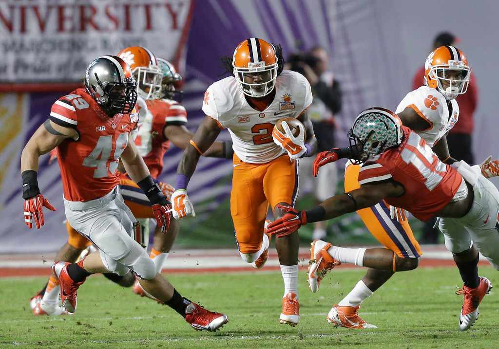 Description of . Clemson wide receiver Sammy Watkins (2) runs between Ohio State defenders during the first half of the Orange Bowl NCAA college football game, Friday, Jan. 3, 2014, in Miami Gardens, Fla. (AP Photo/Wilfredo Lee)