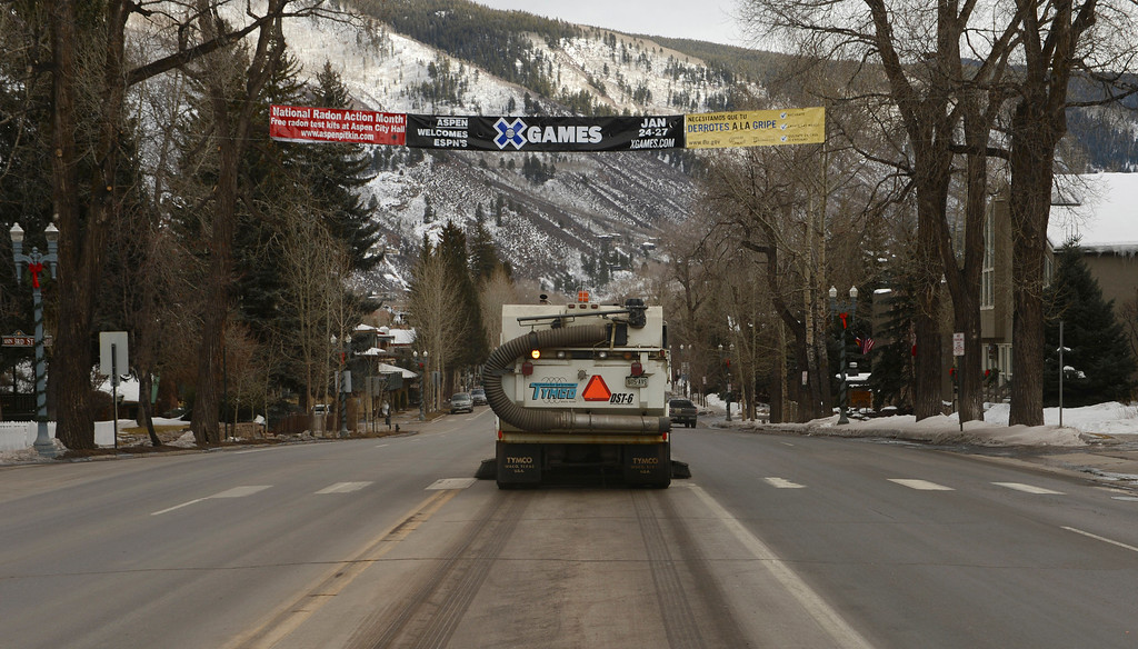 Description of . ASPEN, CO. - JANUARY 24:  The 2013. Winter X Games officially kicked off in Aspen. A street sweeper cleans Main Street in downtown Aspen, January 24, 2013,as visitors start to arrive in town. (Photo By RJ Sangosti / The Denver Post)