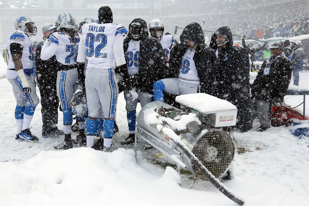 Description of . Detroit Lions players warm themselves during the first half of an NFL football game against the Philadelphia Eagles, Sunday, Dec. 8, 2013, in Philadelphia. (AP Photo/Matt Rourke)
