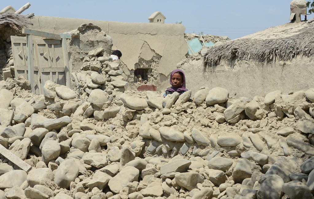 Description of . A Pakistani earthquake survivor looks out from her collapsed mud house at Labach area, in the earthquake-devastated district of Awaran on September 26, 2013. Tens of thousands of survivors of Pakistan's earthquake waited for help in soaring temperatures on September 26 as the death toll rose to nearly 350 and anger grew at the slow pace of government aid. More than 100,000 people made homeless by a 7.7-magnitude quake spent a second night in the open or under makeshift shelters as response teams struggled to reach the remote region in the southwestern province of Baluchistan.  AFP PHOTO / Banaras KHAN/AFP/Getty Images