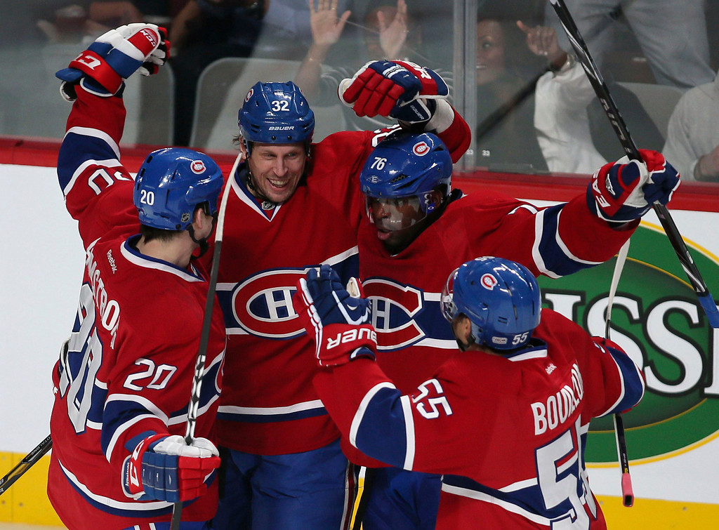 . Montreal Canadiens Travis Moen (32) celebrates his goal on New York goalie Evgeni Nabokov (not shown) with teammates Francis Bouillon (55), P.K. Subban (76) and Colby Armstrong (20) during the first period of NHL hockey action in Montreal, February 21, 2013.  REUTERS/Christinne Muschi