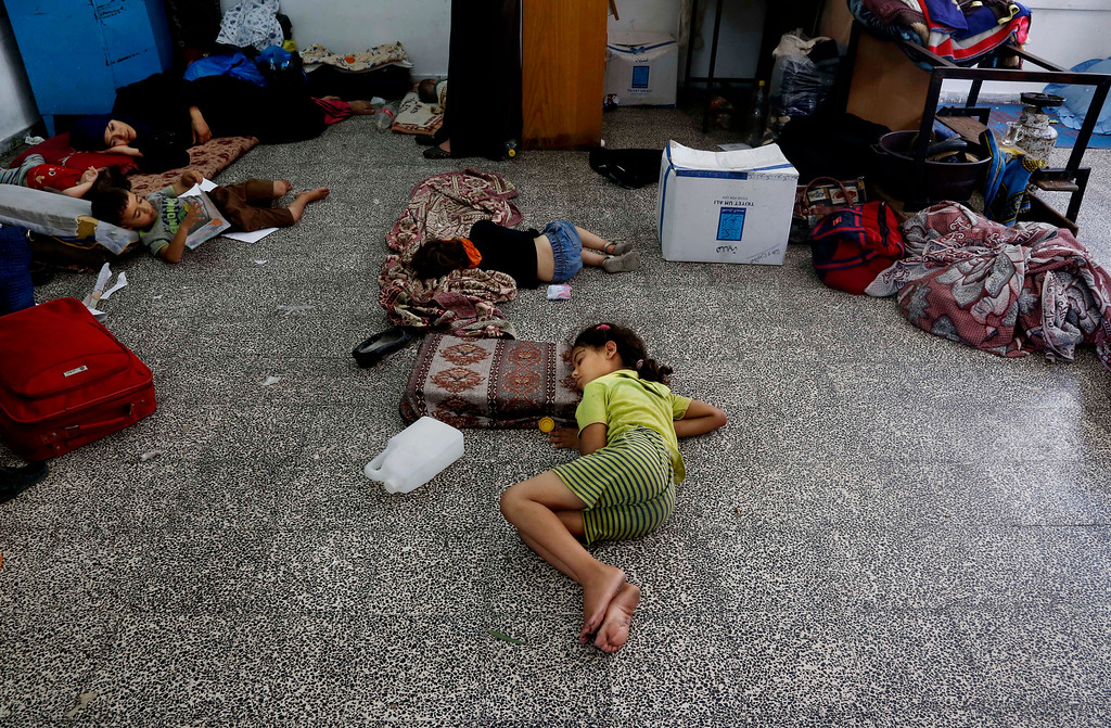 Description of . Palestinian children lay on the floor at the Abu Hussein U.N. school, hit by an Israeli strike earlier, in the Jebaliya refugee camp, northern Gaza Strip, Wednesday, July 30, 2014. Israeli tank shells slammed into a crowded U.N. school sheltering Gazans displaced by fighting on Wednesday, killing more than a dozen and wounding tens after tearing through the walls of two classrooms, a spokesman for a U.N. aid agency and a health official said. The Israeli military said mortar shells had been fired from near the school, and that soldiers fired back. (AP Photo/Hatem Moussa)