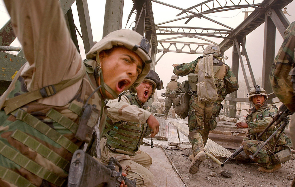 Description of . U.S. Marines from the 3rd Batallion yell to urge infantrymen to rush across the damaged Baghdad Highway Bridge, Monday, April 7, 2003, as they moved forward into the city while under fire in the southeastern outskirts of Baghdad. (AP Photo/Boston Herald, Kuni Takahashi)