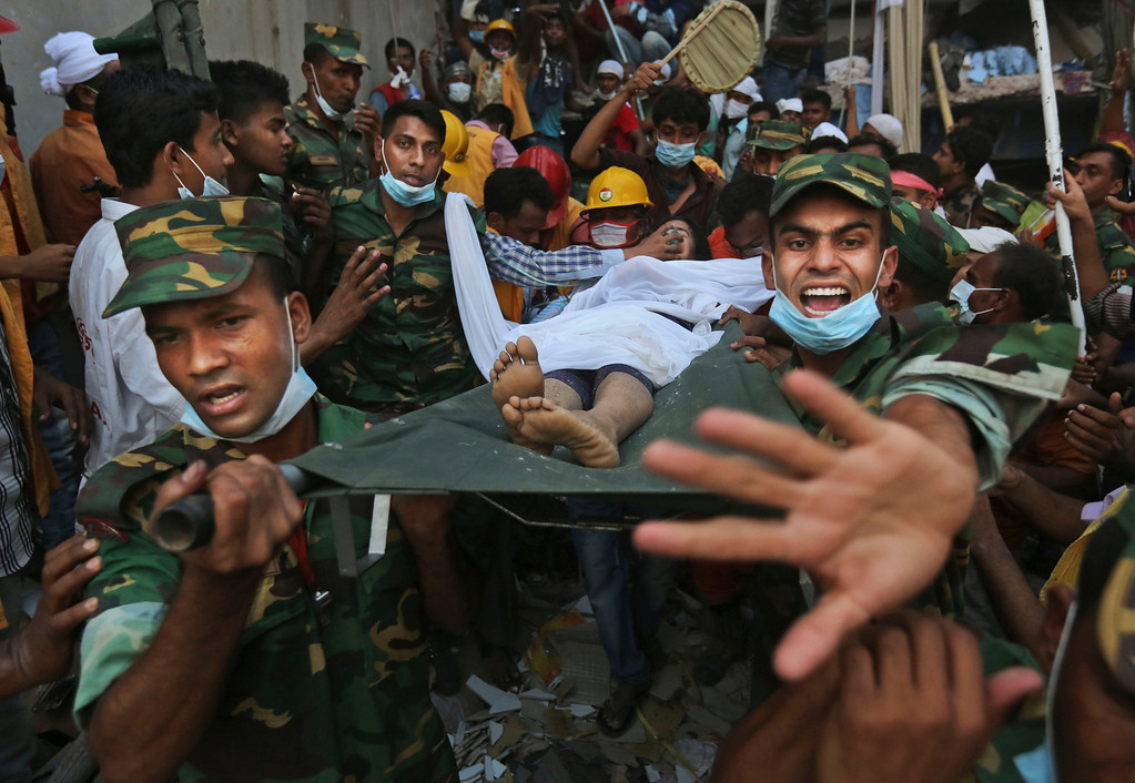 Description of . Bangladesh soldiers carry a woman survivor from the rubble at the site of a building that collapsed Wednesday in Savar, near Dhaka, Bangladesh, Thursday, April 25, 2013. By Thursday, the death toll reached at least 194 people as rescuers continued to search for injured and missing, after a huge section of an eight-story building that housed several garment factories splintered into a pile of concrete.(AP Photo/Kevin Frayer)