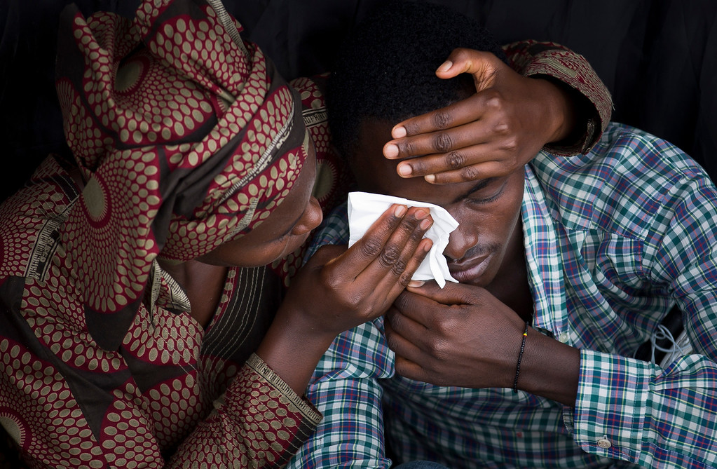 . Bizimana Emmanuel, who was born two years before the genocide, is consoled by an unidentified woman while attending a public ceremony to mark the 20th anniversary of the Rwandan genocide, at Amahoro stadium in Kigali, Rwanda,  Monday, April 7, 2014. (AP Photo/Ben Curtis)