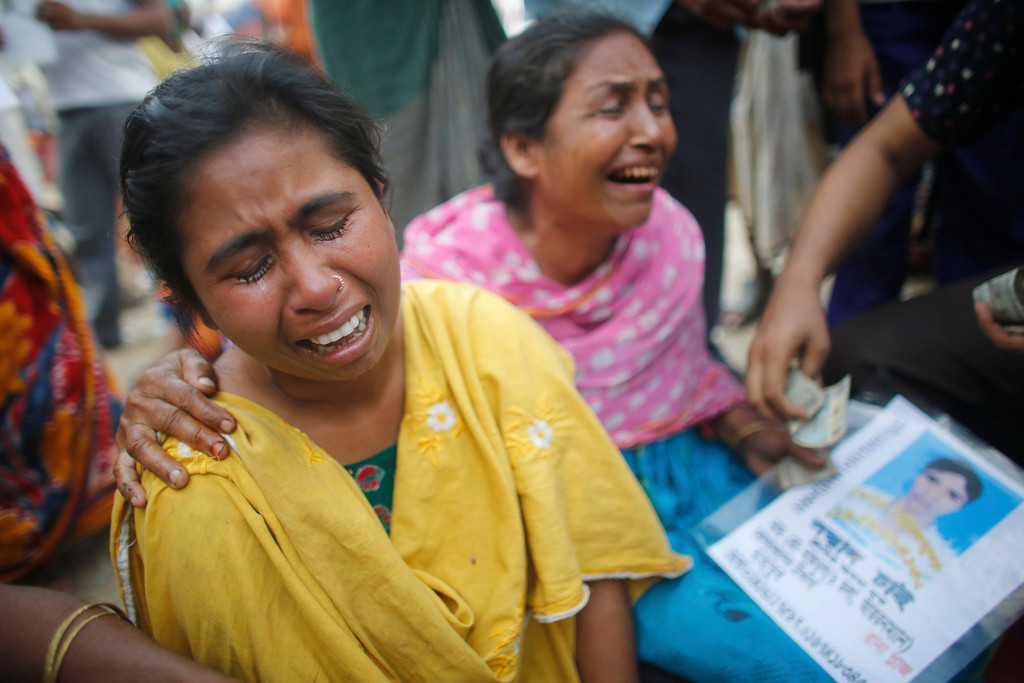 Description of . Women cry as they wait for news of their relative, a garment worker who is still missing, after the collapse of the Rana Plaza building in Savar, outside Dhaka April 30, 2013.  REUTERS/Andrew Biraj