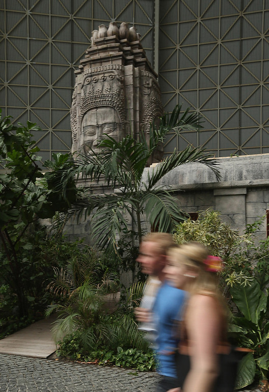 Description of . Visitors walk past a miniature recreation of Angkor Wat at the Tropical Islands indoor resort on February 15, 2013 in Krausnick, Germany. Located on the site of a former Soviet military air base, the resort occupies a hangar built originally to house airships designed to haul long-distance cargo. Tropical Islands opened to the public in 2004 and offers visitors a tropical getaway complete with exotic flora and fauna, a beach, lagoon, restaurants, water slide, evening shows, sauna, adventure park and overnights stays ranging from rudimentary to luxury. The hangar, which is 360 metres long, 210 metres wide and 107 metres high, is tall enough to enclose the Statue of Liberty.  (Photo by Sean Gallup/Getty Images)