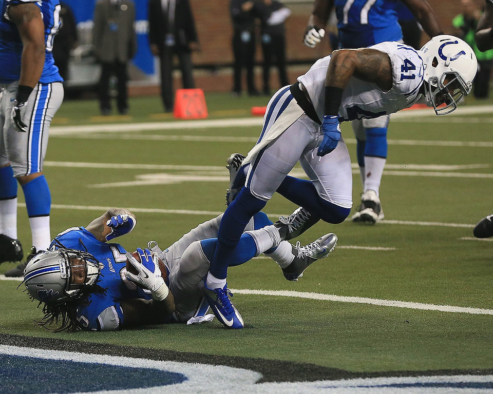 Description of . Mikel Leshoure #25 of the Detroit Lions dives in the end zone for a touchdown under Antoine Bethea #41 of the Indianapolis Colts at Ford Field on December 2, 2012 in Detroit, Michigan.  (Photo by Dave Reginek/Getty Images)