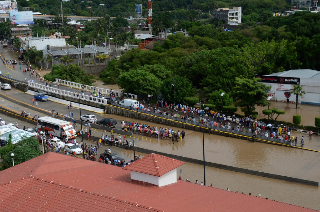 Description of . People stand next to a flooded road in the city of Acapulco, Mexico, Tuesday Sept. 17, 2013. The death toll rose to 47 Tuesday from the unusual one-two punch of a tropical storm and a hurricane, hitting Mexico at nearly the same time. Authorities scrambled to get help into, and stranded tourists out of, the cutoff resort city. (AP Photo/Bernandino Hernandez)