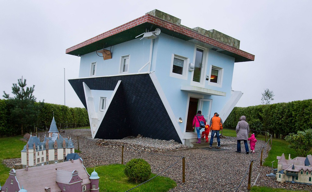 Description of . Visitors enter a house standing upside down in Trassenheide on the Baltic Sea island of Usedom, northeastern Germany, on November 2, 2013. The house was already constructed in the year 2008 by two Polish initiators, who also designed the house\'s interior upside down.      AFP PHOTO / DPA / JENS BUETTNER / /AFP/Getty Images