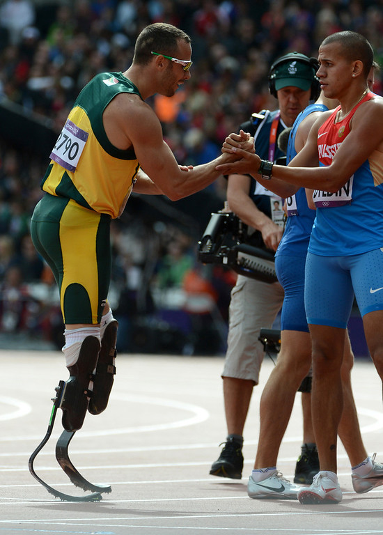 Description of . South Africa's Oscar Pistorius, left, shakes hands with Russia's Maksim Dyldin after their Men's 400m heat at the Olympic Stadium for the London 2012 Olympics in London, England on Saturday, Aug. 4, 2012.  (Nhat V. Meyer/Mercury News)