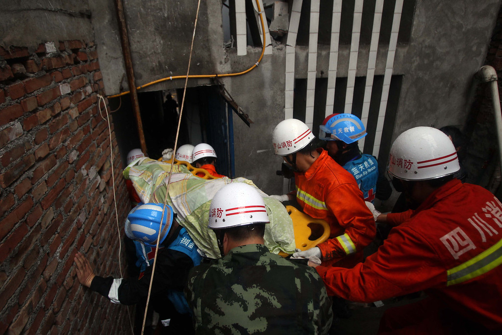 Description of . LUSHAN, CHINA - APRIL 23:  (CHINA OUT) Rescuers carry a victim's body out of a damaged building on April 23, 2013 in Lushan County, China. A powerful earthquake struck the steep hills of China's southwestern Sichuan province on the morning of April 20, leaving at least 193 people dead and more than 12,200 injured.  (Photo by ChinaFotoPress/Getty Images)