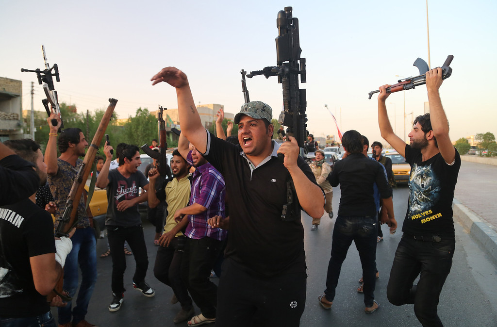 Description of . Shiite tribal fighters raise their weapons and chant slogans against the al-Qaida-inspired Islamic State of Iraq and the Levant (ISIL) in Basra, Iraq's second-largest city, 340 miles (550 kilometers) southeast of Baghdad, Iraq, Sunday, June 15, 2014. Emboldened by a call to arms by the top Shiite cleric, Iranian-backed militias have moved quickly to the center of Iraqís political landscape, spearheading what its Shiite majority sees as a fight for survival against Sunni militants who control of large swaths of territory north of Baghdad. (AP Photo/ Nabil Al-Jurani)