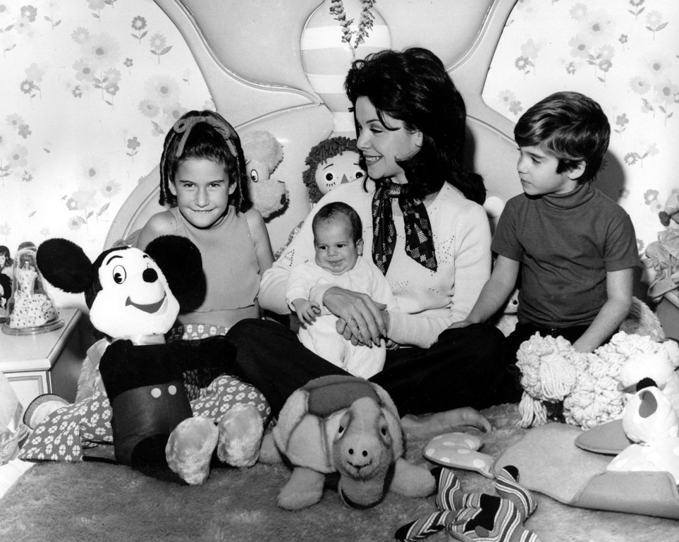 Description of . Actress and former Mouseketeer Annette Funicello holds her infant son, 7-month-old Jason, while watching a revival TV show of the old Mickey Mouse Club series with 9-year-old daughter Gina, and 5-year-old son Jack Jr., at her home in Burbank, Calif., on March 11, 1975. (AP Photo)