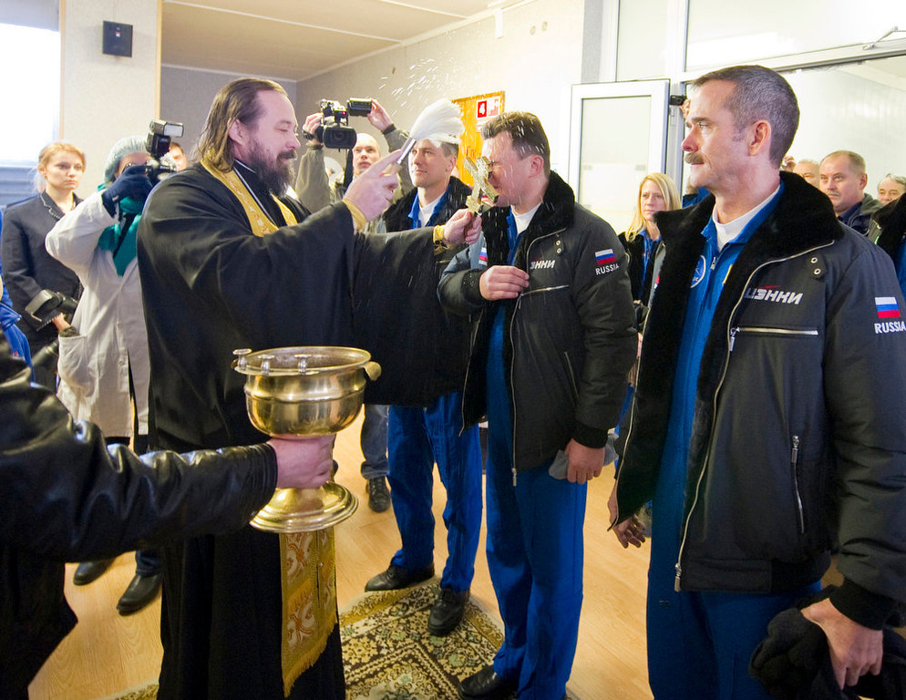 Description of . An Orthodox priest blesses the International Space Station (ISS) crew members from left to right in blue overall., U.S. astronaut Thomas Marshburn, Russian cosmonaut Roman Romanenko and Canadian astronaut Chris Hadfield before they leave a hotel for a final pre-launch preparation at the Baikonur Cosmodrome, Wednesday, Dec. 19, 2012.  (AP Photo/Sergei Remezov, Pool)