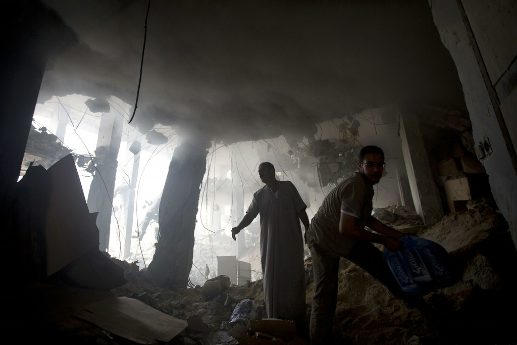 Description of . Palestinian men remove goods from the rubble of a destroyed store located on the ground floor of a building hit by an Israeli air strike on July 22, 2014 in Gaza city. UN chief Ban Ki-moon and US Secretary of State John Kerry are in Cairo today in a bid to broker a truce between Israel and Hamas after two weeks of fighting which has left over 570 Palestinians dead. AFP PHOTO / MAHMUD HAMS/AFP/Getty Images