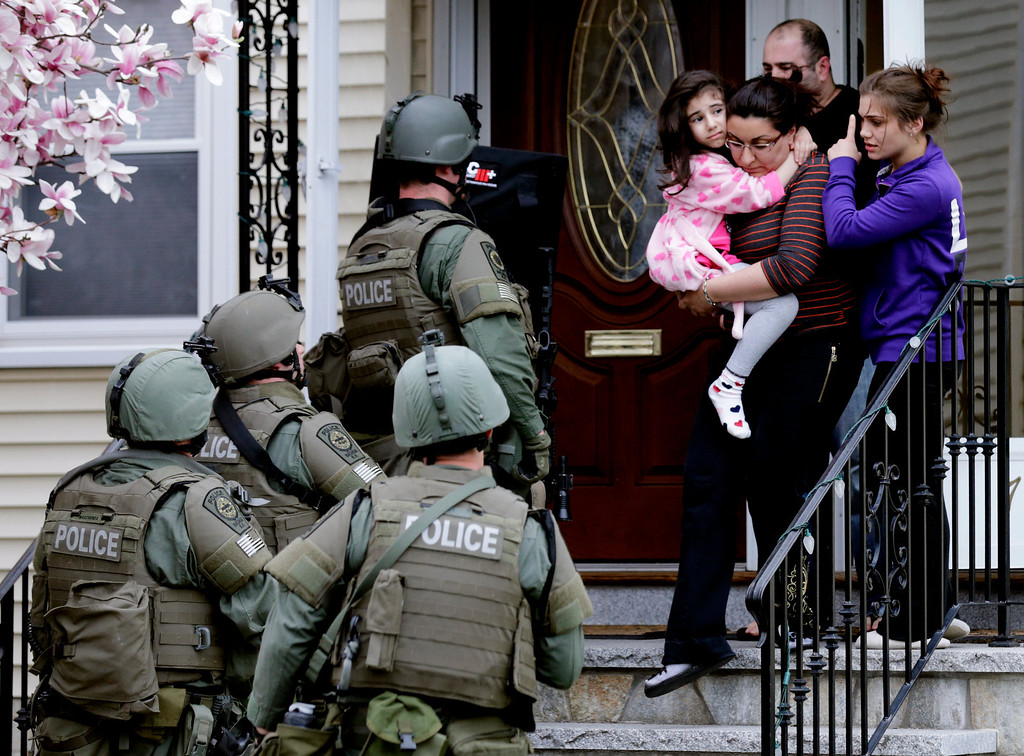 Description of . A woman carries a girl from their home as a SWAT team searching for a suspect in the Boston Marathon bombings enters the building in Watertown, Mass., Friday, April 19, 2013. (AP Photo/Charles Krupa)