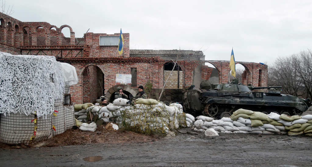 Description of . Ukrainian soldiers guard a check point near the town of Debaltseve, Ukraine, Monday, Feb. 2, 2015. As fighting intensifies between government and rebel forces for control over a key railway hub in the eastern Ukraine town of Debaltseve, separatist leader Alexander Zakharchenko said Monday that he plans to mobilize enough new volunteers to bring his forces to 100,000 men. (AP Photo/Petr David Josek)