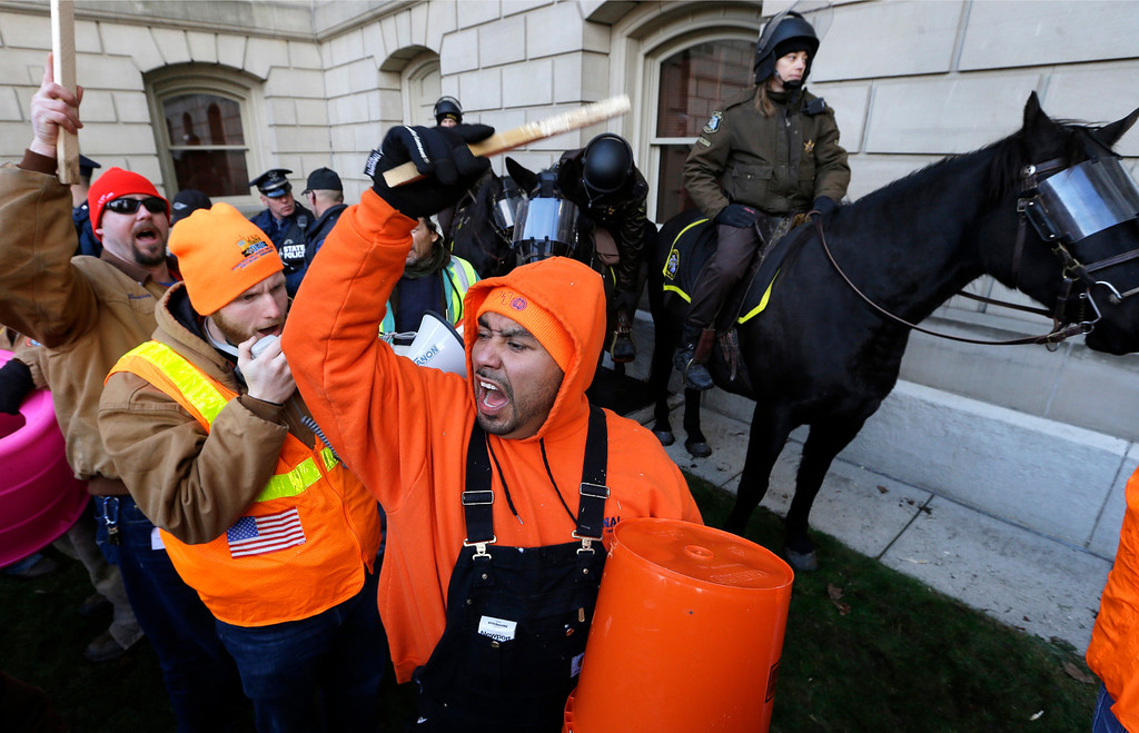 Description of . Armando Ramos, of Saginaw, Mich., protests during a rally at the State Capitol in Lansing, Mich., Tuesday, Dec. 11, 2012. The crowd is protesting right-to-work legislation passed last week. Michigan could become the 24th state with a right-to-work law next week. Rules required a five-day wait before the House and Senate vote on each other's bills; lawmakers are scheduled to reconvene Tuesday and Gov. Snyder has pledged to sign the bills into law. (AP Photo/Paul Sancya)