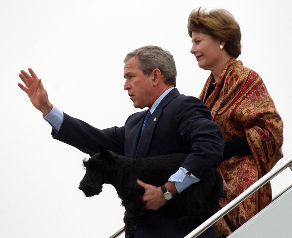 Description of . President Bush waves as he carries his dog Barney as he leaves Air Force One with first lady Laura Bush at Texas State Technical College airport in Waco, Texas, Friday, Dec. 26, 2003. Bush and his family will spend the New Year's Days holiday at their Crawford, Texas ranch.  (AP Photo/Susan Walsh)