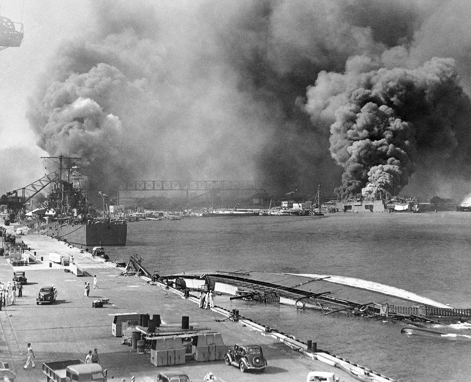 Description of . In this image provided by the U.S. Navy, a pall of smoke filled the sky over Pearl Harbor, Hawaii on Dec. 7, 1941, after the Japanese attacked. In the foreground is the capsized minelayer, the USS Oglala, and to the left appears the moored USS Helena, 10,000-ton cruiser, struck by a bomb. Beyond the superstructure of the USS Pennsylvania, and at the right is the USS Maryland, burning. At right center the destroyer Shaw is ablaze in drydock. (AP Photo/U.S. Navy)