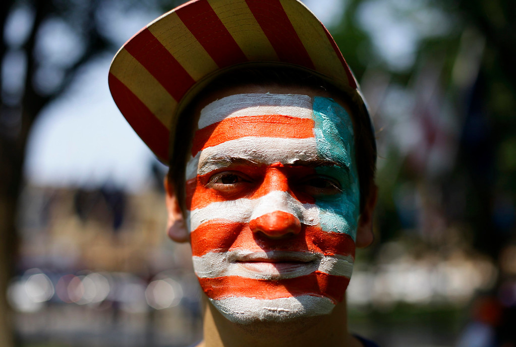 Description of . A man with the American flag painted on his face poses for a portrait as he celebrates the Fourth of July Independence Day celebrations in Prescott, Arizona July 4, 2013. REUTERS/Joshua Lott